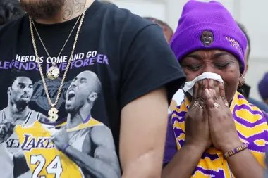 Una simpatizante parece rezar por Kobe Bryant, que estuvo omnipresente en la vestimenta de la gente: