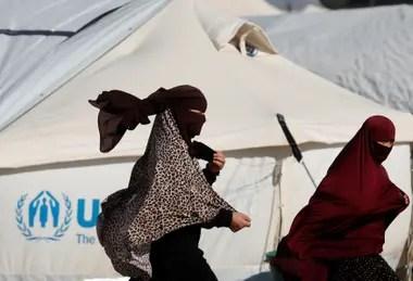 Las mujeres pasan junto a una carpa en el campamento de al-Hol