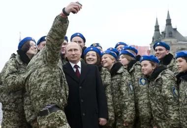 El presidente ruso Vladimir Putin posa para una selfie con jóvenes activistas en la Plaza Roja de Moscú
