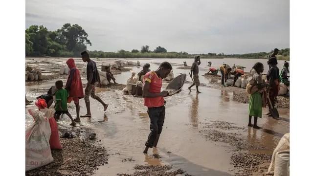 Los trabajadores tamizan la tierra en el río en busca de gemas