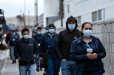 Los trabajadores de producción con máscaras llegan para su turno a la planta Hyundai en Tijuana, estado de Baja California, México, el 18 de mayo de 2020, en medio de la pandemia de coronavirus