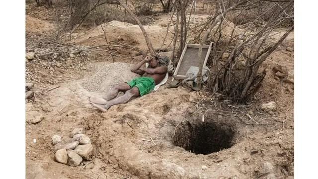 Un minero descansa junto al agujero de la mina