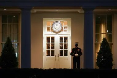A Marine guards the entrance to the West Wing at the White House