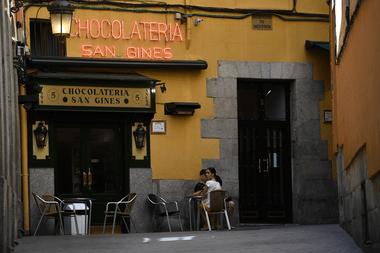 Las personas se sientan en la chocolatería San Ginés en Madrid el 25 de mayo de 2020, luego de que las medidas de bloqueo del coronavirus finalmente se flexibilizaron para las personas en Madrid y Barcelona