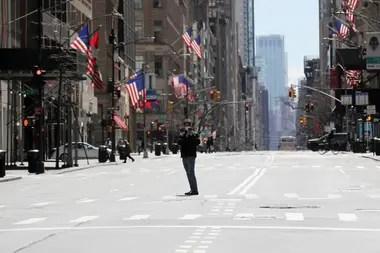 Un hombre se detiene en el medio de la Quinta Avenida, totalmente vacía, para tomarse una selfie