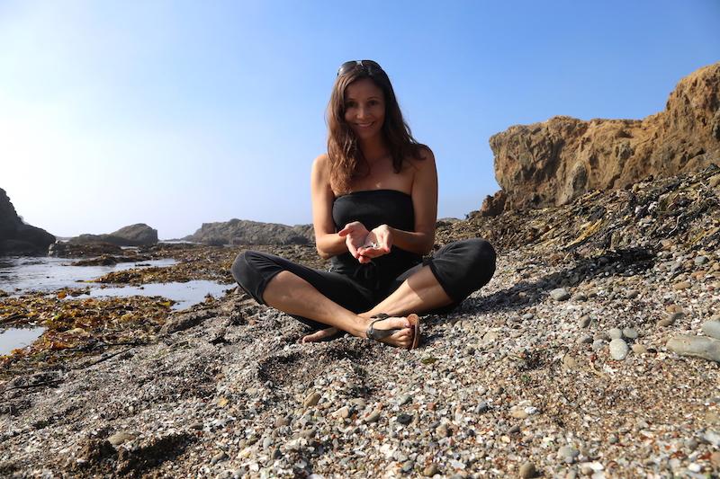 Annette White sitting on Glass Beach in Fort Bragg