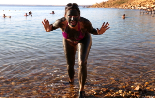 Annette White covered in The Dead Sea mud in Jordan