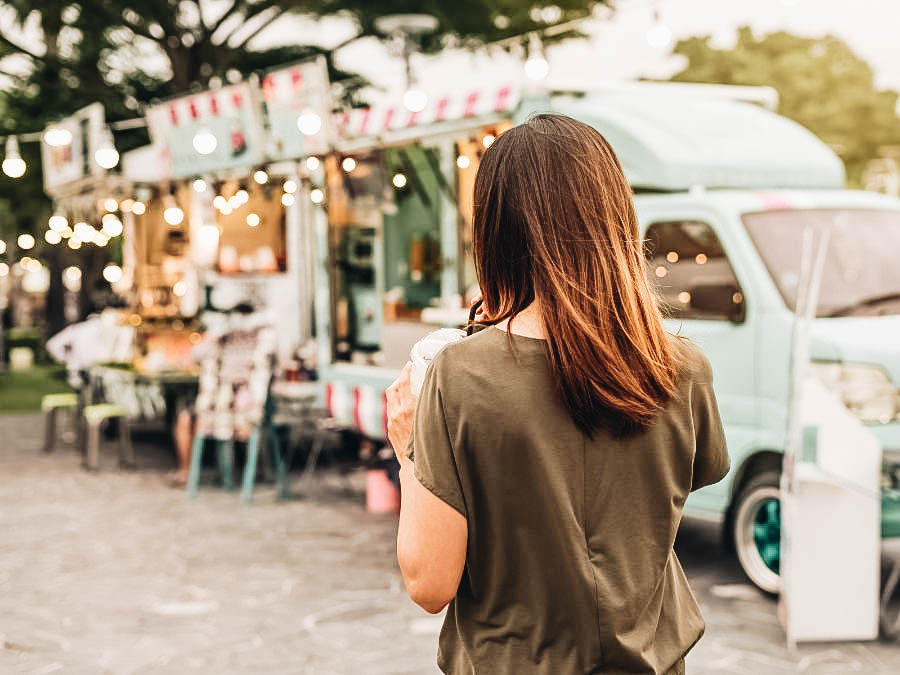 A woman walking to a food truck