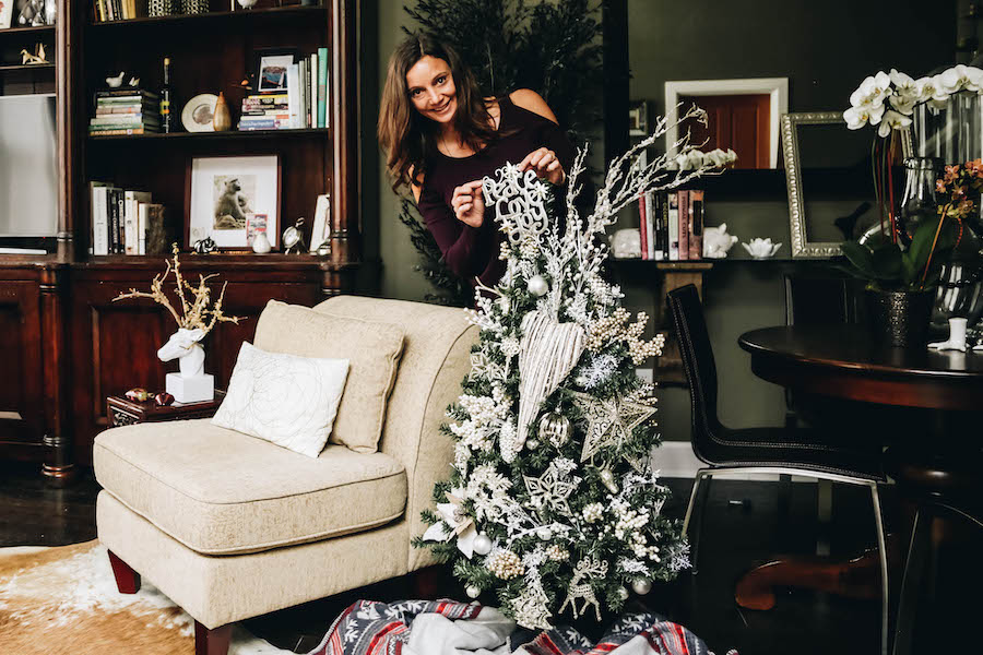 Annette White decorating a Christmas Tree