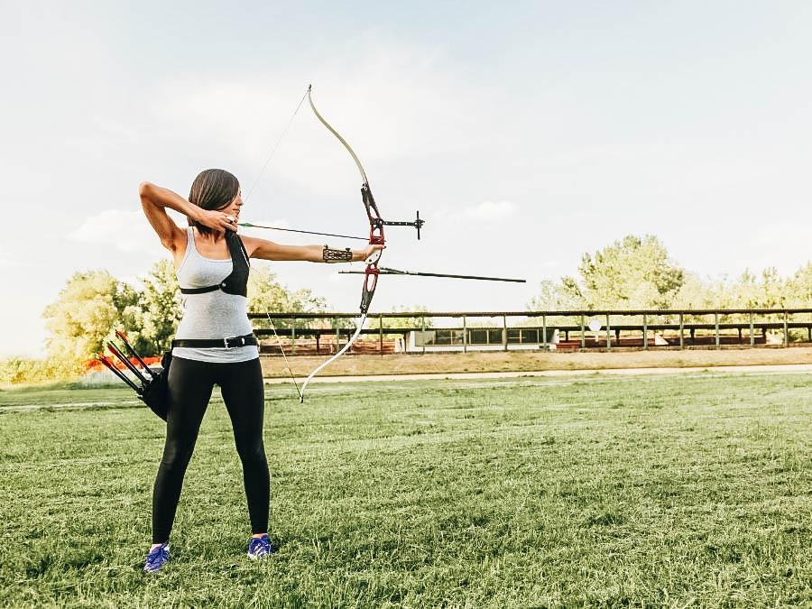 A girl doing Archery on a Field