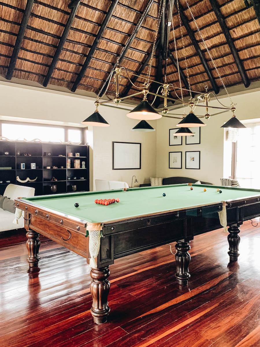 A billiard table inside a game room