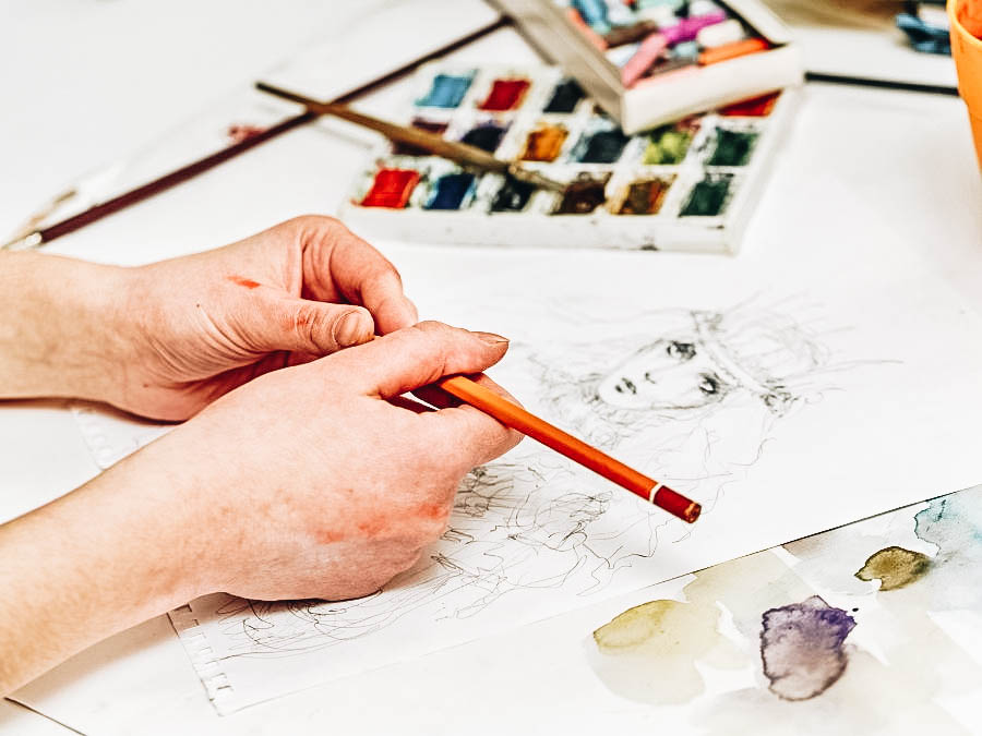 A man creating a lovely drawing using his pencil and water color