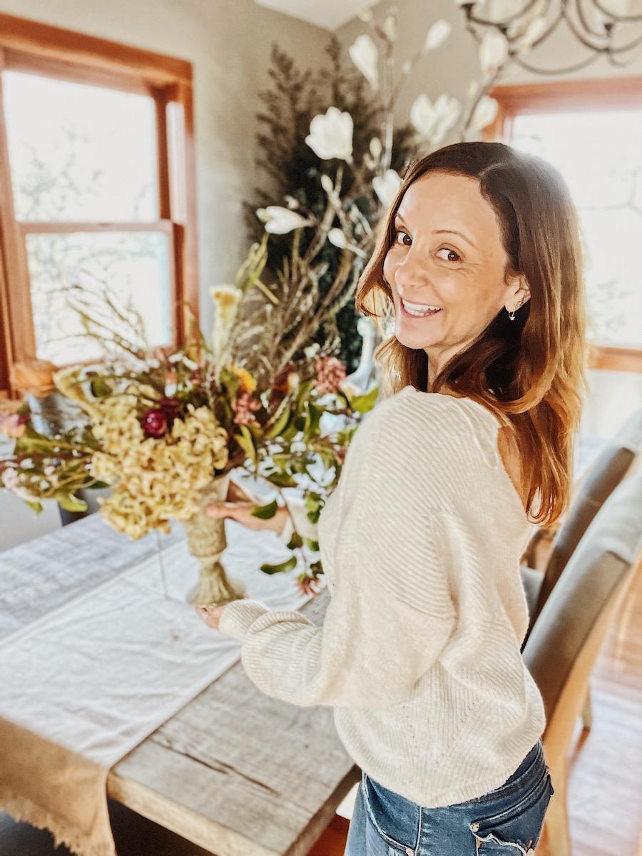 Annette holding a flower arrangement at home