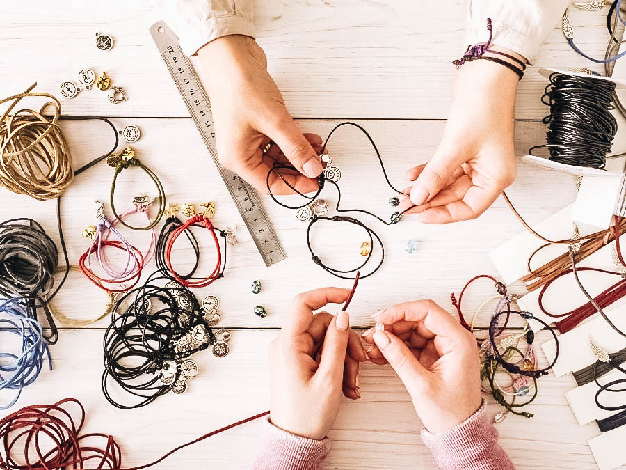 Two people making jewelries using strings and beads