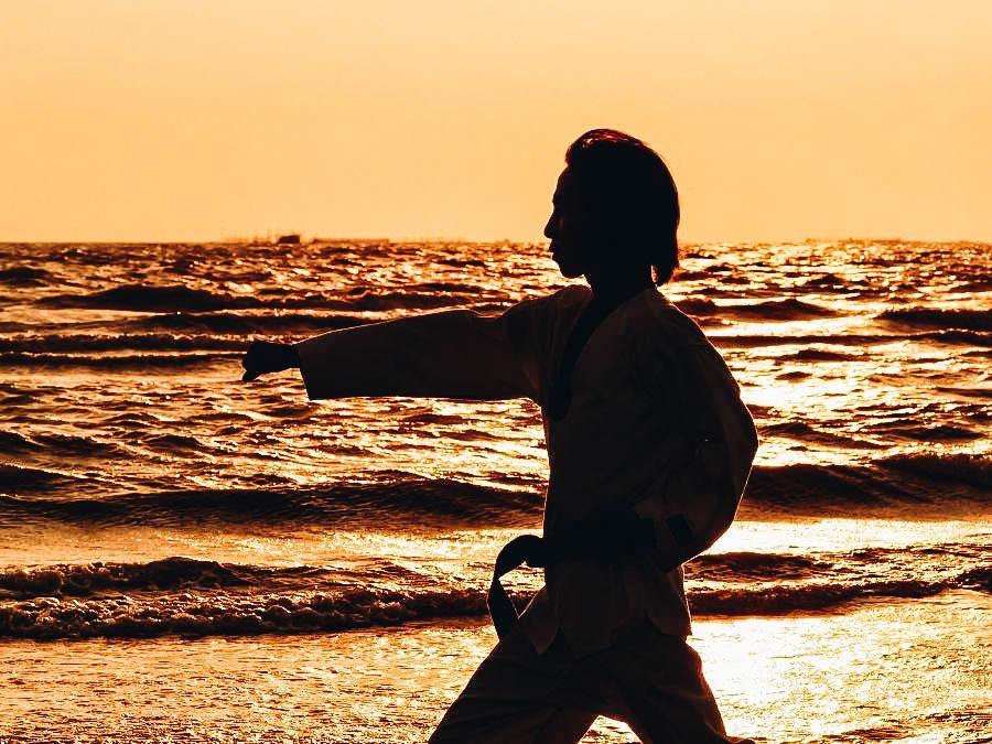 A martial artist practicing on a beach