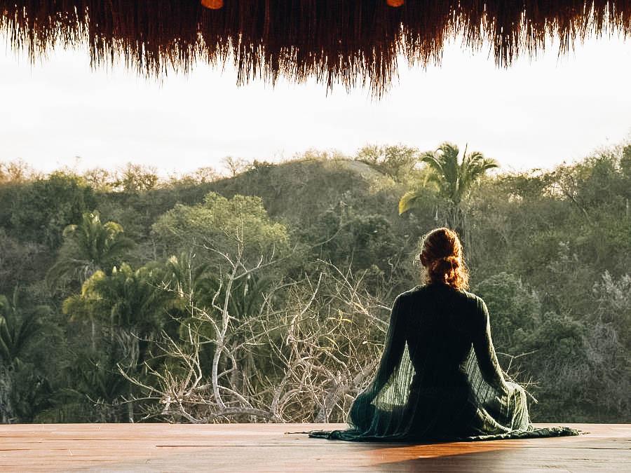 A girl meditating near a beautiful forest