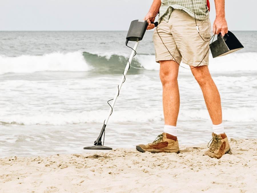 A man using his metal detector near the beach