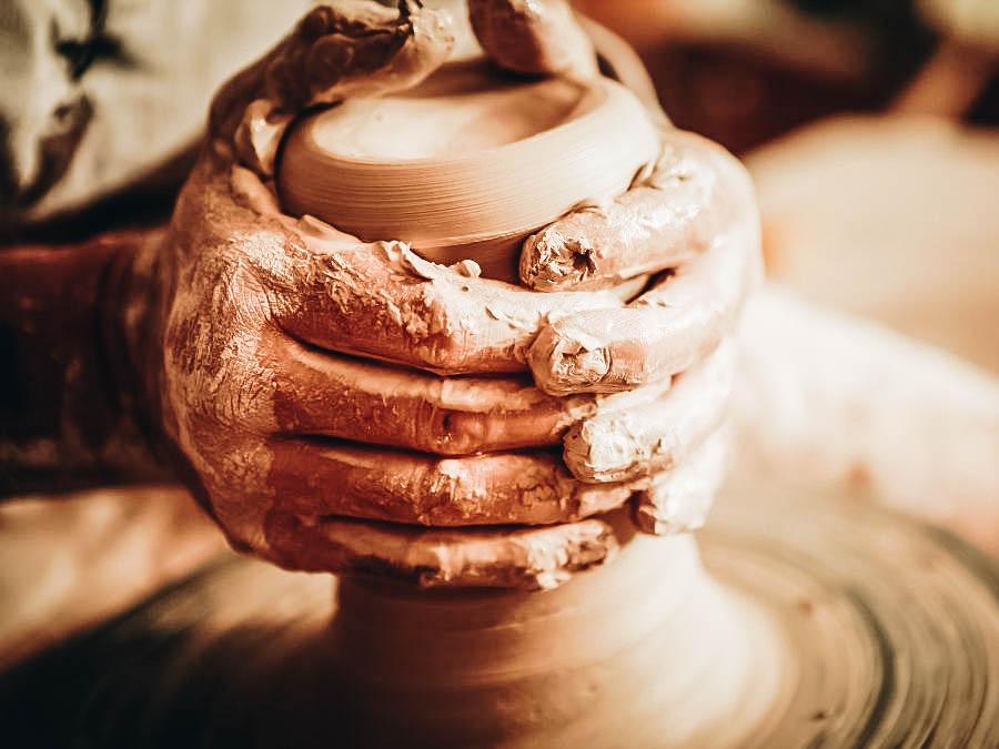 A person molding a clay pot