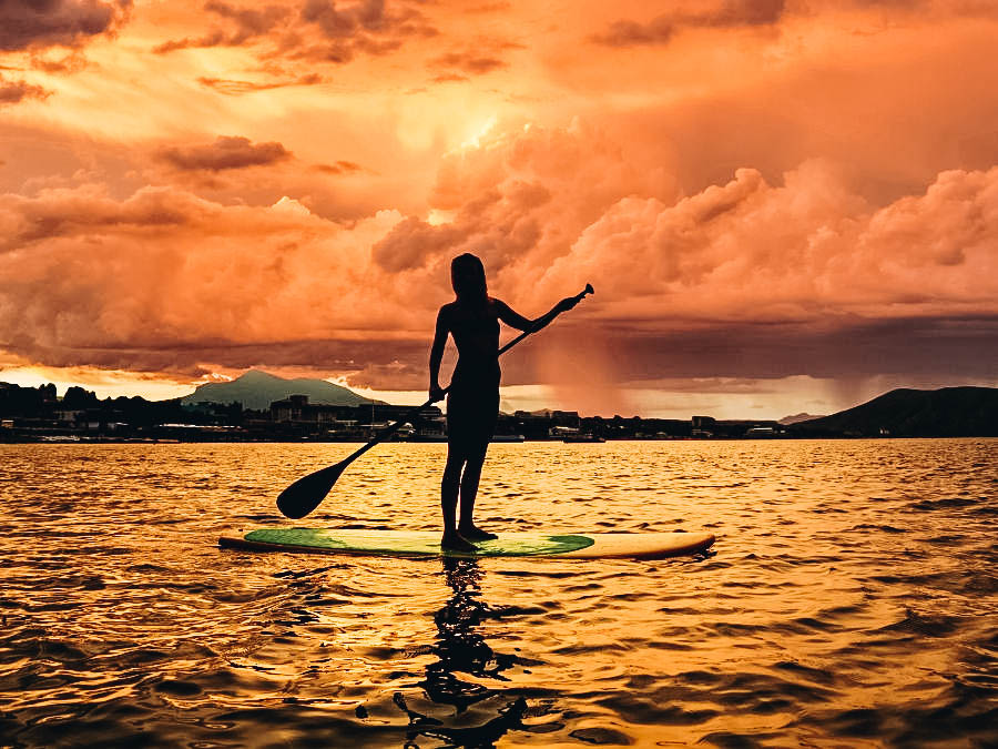 A girl stand paddle boarding on a sunset