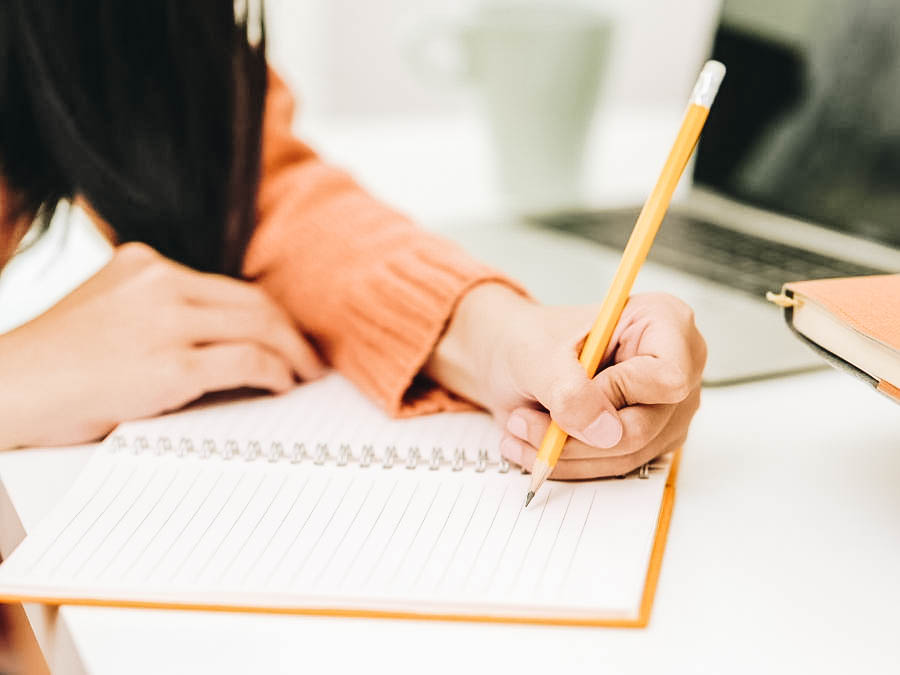 A person writing on a notebook using a pencil