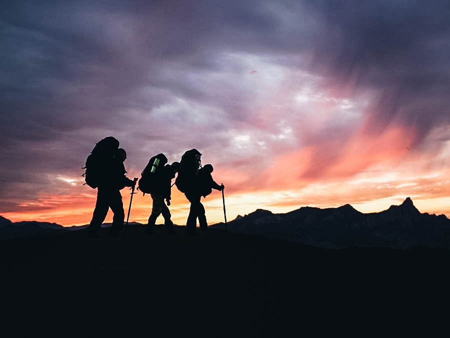 Three people hiking on sunrise