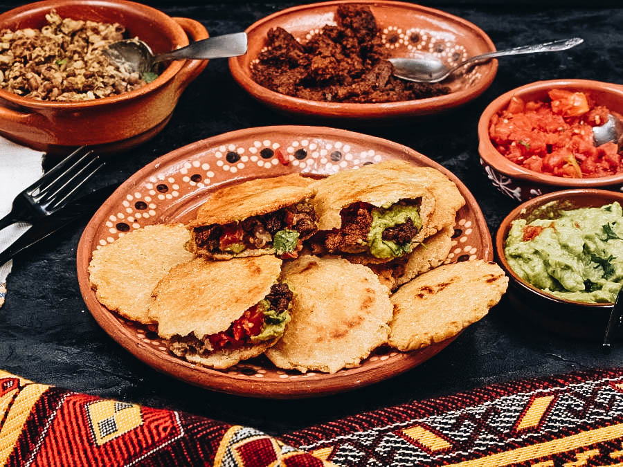 Gorditas served on a table with other Mexican delicacies