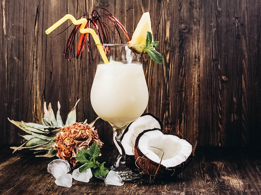 A Pina Colada Cocktail with Pineapples and Coconuts on the side
