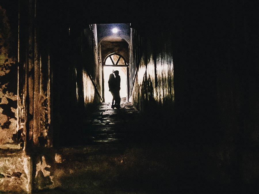 A couple standing on the entrance of a dark hallway