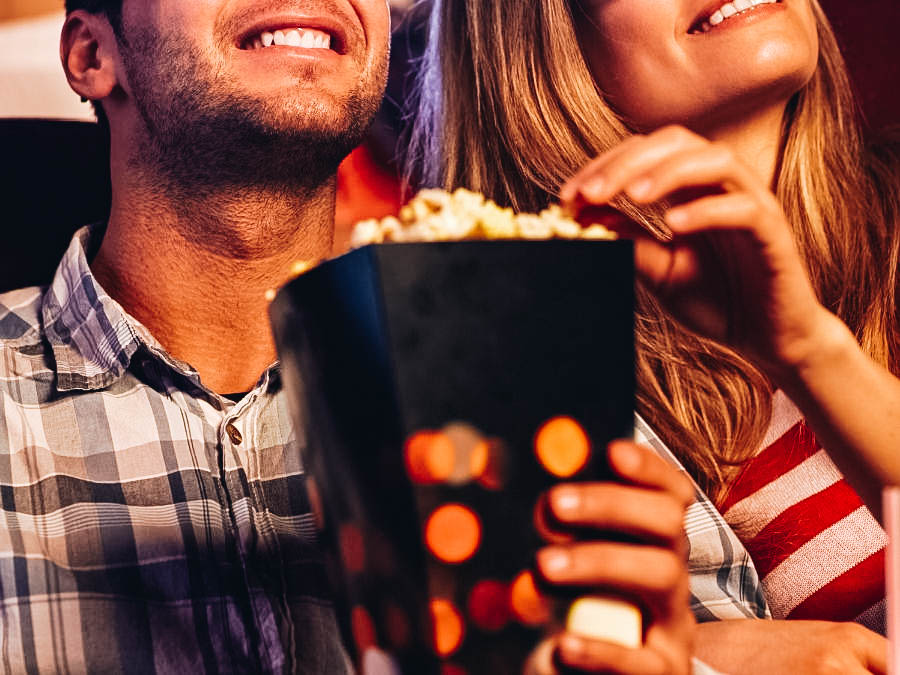 A couple eating popcorns while having movie night