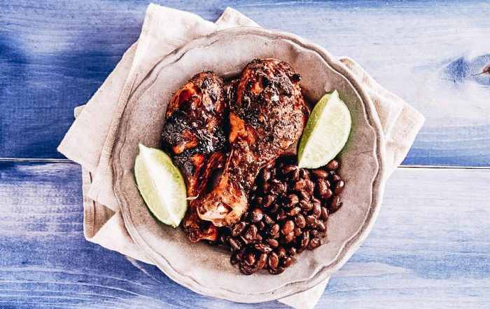 A native Jamaican Jerk chicken on a blue table