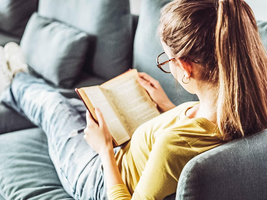 A woman reading a book on the couch