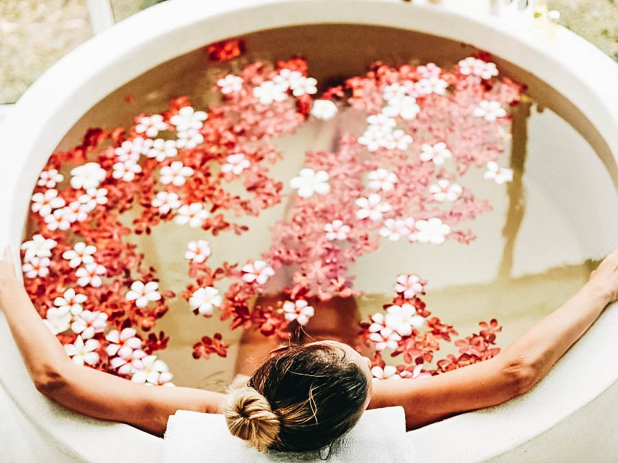 A woman relaxing on a flower bath