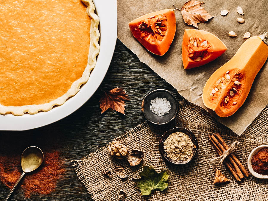 Baked pumpkin pie and it's ingredients on a table