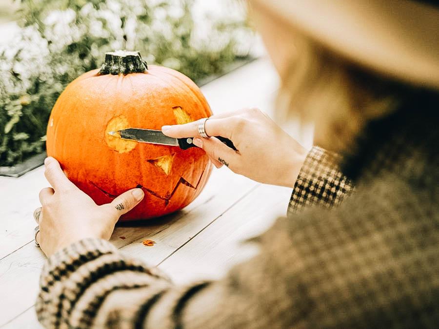A guy carving a pumpkin