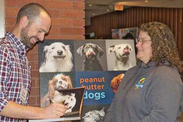 Photographer Greg Murray signing a copy of his book Peanut Butter Dogs.