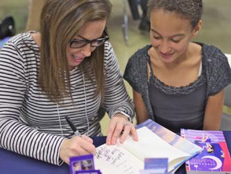 Author Rachele Alpine signs a book for a fan.