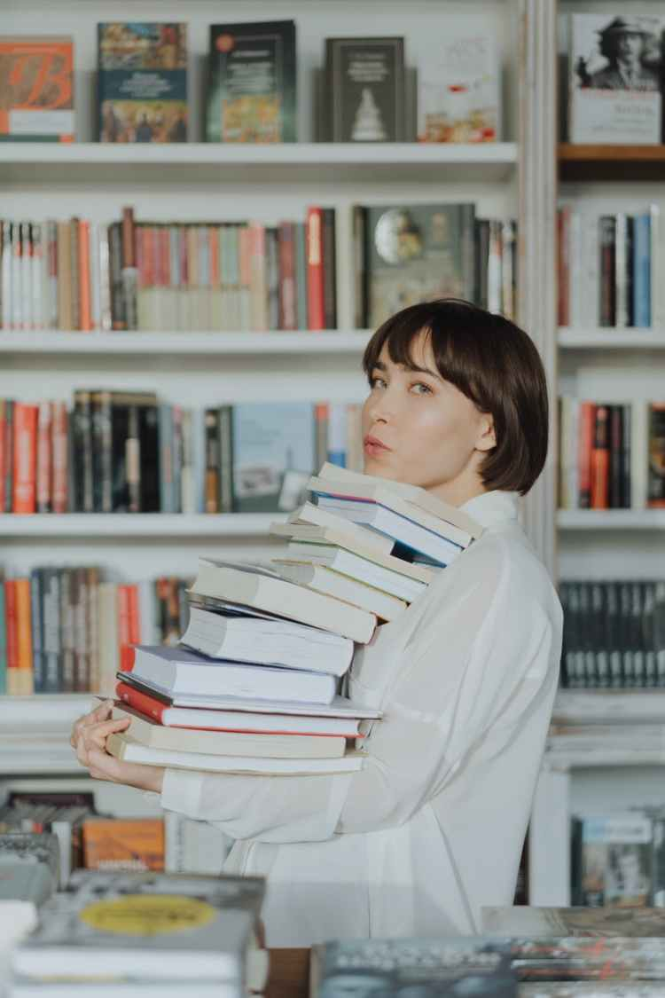 woman in white long sleeve shirt carrying a stack of books
