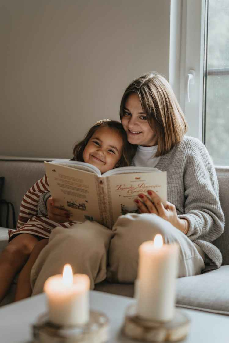 a mother and daughter reading a book on a couch