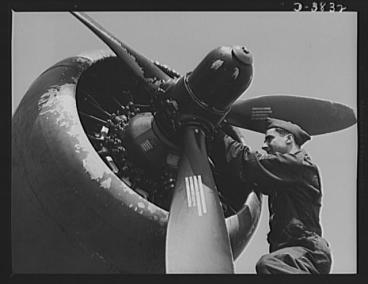 An airplane mechanic works on a plane's propeller.