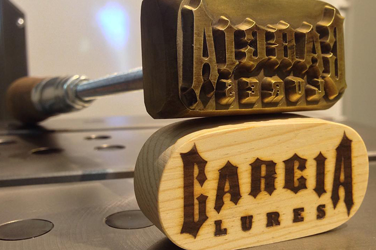 custom steel logo stamp shows Garcia Lures logo stamped into wood by Buckeye Engraving