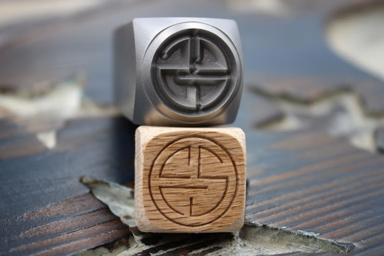 face grain wood stamped with CCS wood logo stamp with steel hand stamp used to mark it lying on top of the marked piece of wood