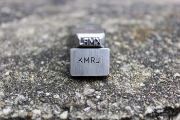 custom steel hand stamp crafted by Buckeye Engraving shows KMRJ initials stamped in steel square resting on stone