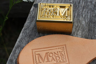brass custom leather hand stamp show Monk Made USA logo and piece of debossed leather with logo