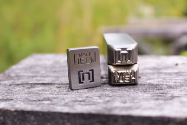 three custom steel press stamps show different versions of Matt Helm logo crafted by Buckeye Engraving