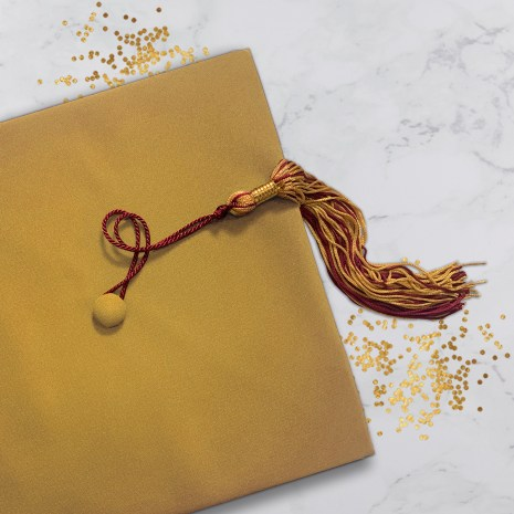 Old gold graduation cap with maroon and gold tassel