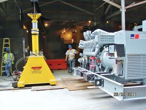 A slideshow of the Master Riggers at Budco using forklifts and hydraulic jacking gantries with chainfalls to rig a generator through a floor hatch into the basement.
