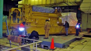 The Master Riggers at Budco were tasked with rigging generators into a loud basement equipment room. Special ear protection with noise cancelling intercoms were utilized so our crew could safely communicate in the environment. The generators had to first be lifted by a crane in the driveway and set down in front of the doorway to the equipment room. A runway system was created to keep pressure off the floor and they were rigged into their final positions using gantries, forklifts, and skates.