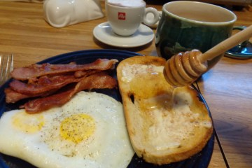 Breakfast of champions - eggs, bacon, cappucino and honey on toast
