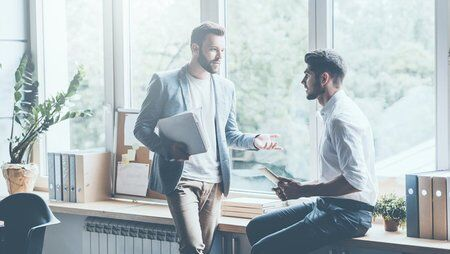 sa_1618761454_two-men-talking-office