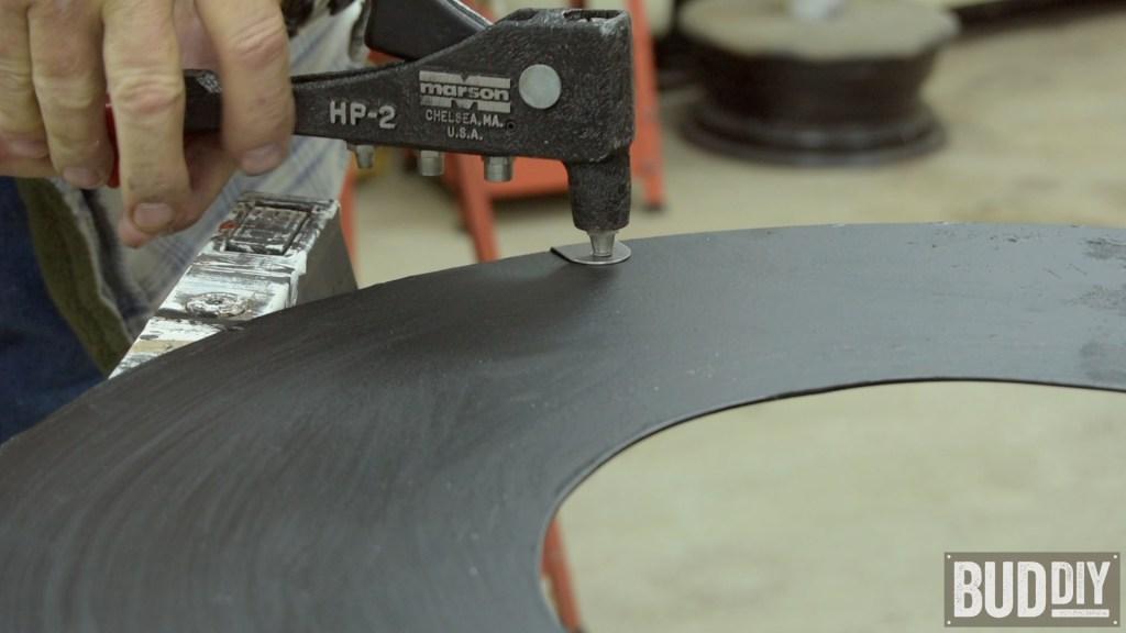pop rivet the strap bracket to metal base